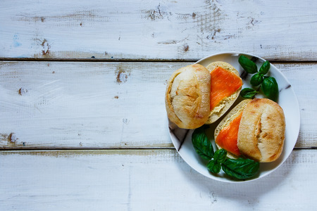 Sandwiches with cream cheese and smoked salmon on rustic wooden background. Top view, copy space