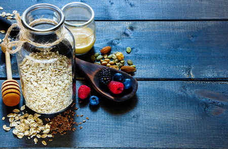 Close up of diet breakfast ingredients. Open jar with oatmeal, fresh berries in old wooden spoon, creamed honey, nuts and pumpkin seeds over dark rustic background, selection focus, copy space