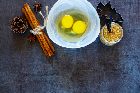 tinting: Christmas New Year bakery recipe vintage background with baking ingredients (eggs, brown sugar, cinnamon and vanilla sticks) and baking utensils on dark backdrop. Top view, copy space