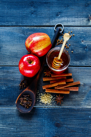 Close up of various winter warming spices and apples for baking or cooking mulled wine. Cinnamon, carnation cloves, anise, honey and brown sugar over old dark plywood background, top view