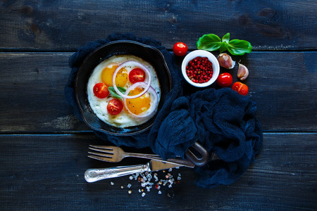 Top view of breakfast set in rural style over wooden background. Old pan of fried eggs, onion, basil and fresh tomatoes on dark table surface, flat lay.
