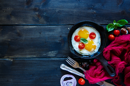 Old pan of fried eggs, basil and cherry-tomatoes on dark table surface, copy space. Top view of breakfast set in rural style over wooden background.