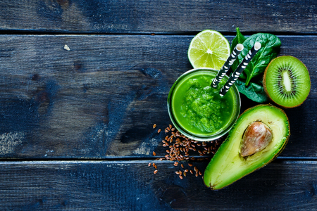Close up of green fresh smoothie with avocado, green fruits and spinach on old wooden dark background, top view. Detox, dieting, clean eating, vegetarian, vegan, fitness, healthy lifestyle concept