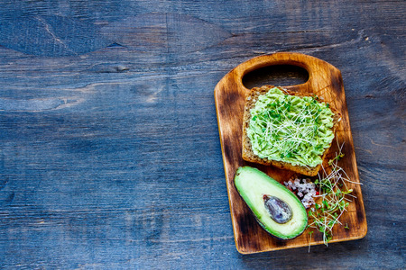 whole wheat toast: Whole wheat toast with avocado and sprouts on vintage wooden board over rustic background, top view, copy space