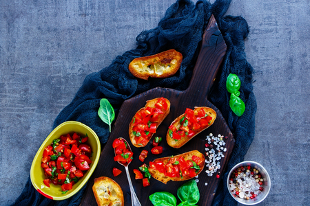 Top view of healthy tomato and basil bruschetta sandwich with ingredients on dark wooden serving board over rustic vintage background. Italian and Vegetarian food concept Reklamní fotografie