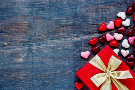 Red Holidays gift and candy hearts on wooden background with space for text, top view. Valentines day background. Stock Photo
