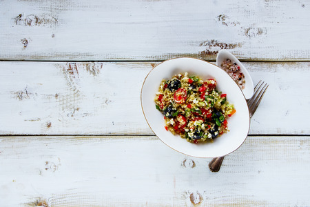 pepperbox: Bowl of homemade healthy quinoa salad with feta cheese, cherry tomatoes, avocado, black olives over white rustic wooden background, top view, copy space. Detox, dieting, vegan, vegetarian, clean eating concept