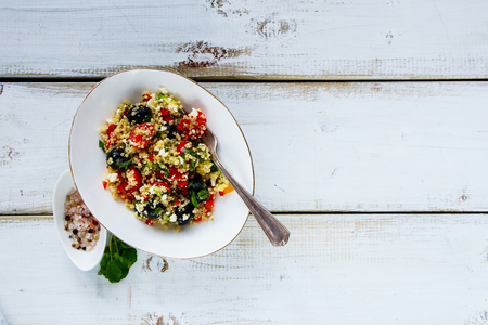 pepperbox: Close up of organic quinoa salad with feta cheese, cherry tomatoes, avocado, black olives in bowl over white rustic wooden background, top view, copy space. Detox, dieting, vegan, vegetarian, clean eating concept