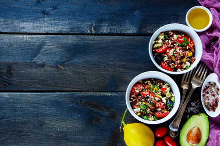 Appetizing red rice salad with feta cheese, cherry tomatoes, avocado, black olives and ingredients on dark vintage wooden background, top view, copy space. Detox, dieting, vegan, vegetarian, clean eating concept