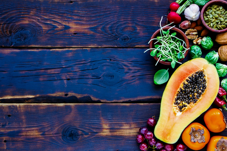 Fresh vegetables and fruits, seeds, nuts, spices, superfoods, herbs, condiment for vegan, allergy-friendly, clean eating and raw diet. Old wooden texture background and top view