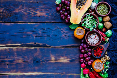 Delicious bio vegetables and fruits, seeds, nuts, spices, superfoods, herbs, condiment for vegan, allergy-friendly, clean eating and raw diet. Old wooden texture background and top view
