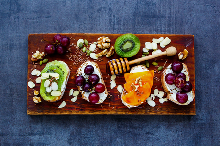 Sweet toast pieces set for breakfast. Wholegrain baguette slices with cream cheese, various fruit, honey, seeds and nuts. Slate background and top view. Clean eating, vegetarian, dieting concept Stock Photo