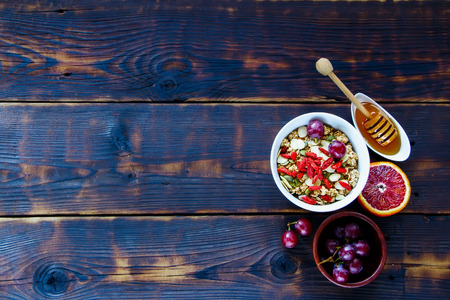 Healthy breakfast concept. Oatmeal, granola in bowl, dried berries, seeds, honey, bloody orange, grapes over dark wooden background, top view. Clean eating, vegan, vegetarian, detox and dieting concept  Imagens