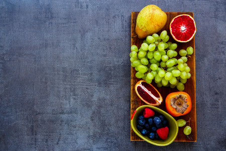 Various organic fruit selection on rustic wooden chopping board over slate background, top view. Agriculture, Gardening, Harvest Concept. Detox, dieting, clean eating, vegan, fitness, healthy lifestyle concept