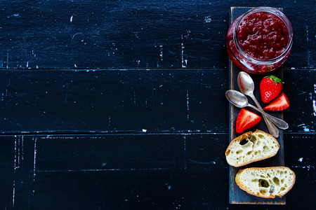Traditional breakfast -  Freshly baked and sliced French baguette with strawberry jam on wooden board over black vintage background, top view, copy space. 版權商用圖片