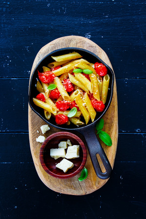 Top view of italian dinner. Pasta penne with roasted tomatoes, basil and parmesan cheese in vintage iron cast pan over dark rustic wood background, flat lay. Slow food concept Stock Photo