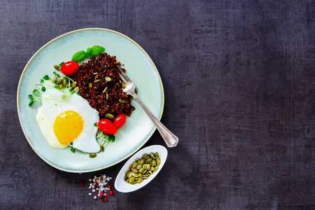 pepperbox: Healthy red quinoa with fried egg, sprouts, tomatoes and pumpkin seeds in plate for tasty dinner on dark rustic slate background, top view, copy space. Detox, dieting, vegan, vegetarian, clean eating concept Stock Photo
