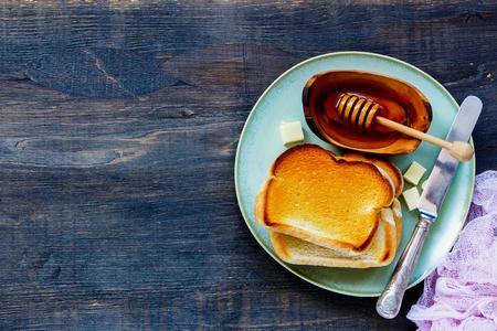 木製の背景, 平面図, コピー スペースをかけて伝統的な朝食プレートの全粒パンのトースト、バターと蜂蜜の閉めます。 写真素材