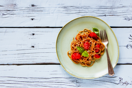 metal grater: Plate of Italian Pasta Spaghetti with roasted tomatoes, fresh basil and parmesan cheese on white rustic wood background, top view, copy space. Slow food concept Stock Photo