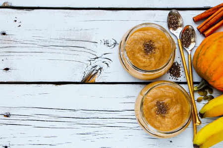 Close up of tasty pumpkin banana smoothie with chia seed in mason jars on white grunge wooden background, top view, copy space. Detox, dieting, vegan, vegetarian, clean eating concept