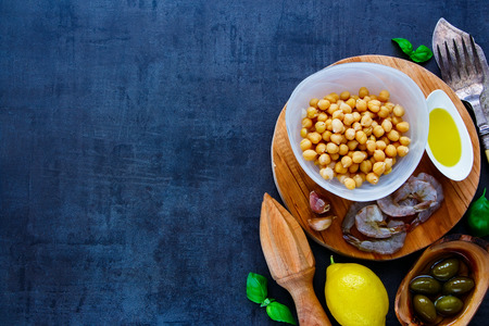 Healthy chickpeas salad ingredients in bowls on round wooden board over dark stone concrete background, top view, copy space. Detox, dieting, vegan, vegetarian, clean eating concept Imagens
