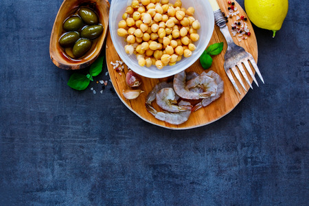 pepperbox: Delicious chickpeas salad ingredients in bowls on round wooden board over dark stone concrete background, top view, copy space. Detox, dieting, vegan, vegetarian, clean eating concept Stock Photo