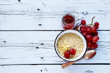 Organic quinoa flakes, honey, almonds and grapes for healthy breakfast on white wooden background. Top view. Flat lay style.