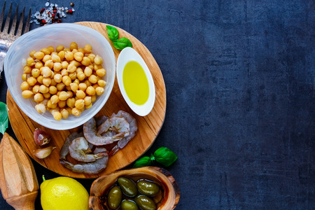 pepperbox: Top view of chickpeas salad ingredients in bowls on round wooden board over dark stone concrete background, copy space. Detox, dieting, vegan, vegetarian, clean eating concept