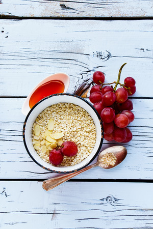 Quinoa flakes, honey, almonds and grapes for healthy breakfast on white wooden background. Top view. Flat lay style.