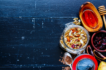Glass jar of homemade oatmeal granola with fruits and nuts on dark vintage background. Top view. Flat lay style. Clean eating, vegan, vegetarian, detox and dieting concept
