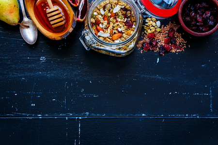 Jar of tasty homemade oatmeal granola with fruits and nuts on dark vintage background. Top view. Flat lay style. Clean eating, vegan, vegetarian, detox and dieting concept