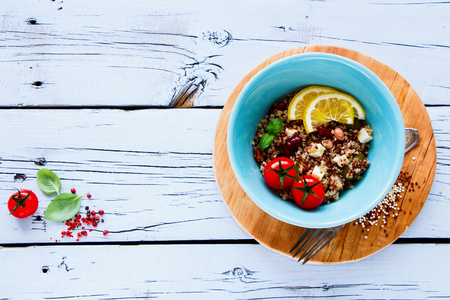 pepperbox: Tasty salad with beans, quionoa, fresh tomatoes, basil, feta cheese and green olives in bowl on white grunge wooden background. Weight loss food concept. Top view. With copy space. Stock Photo