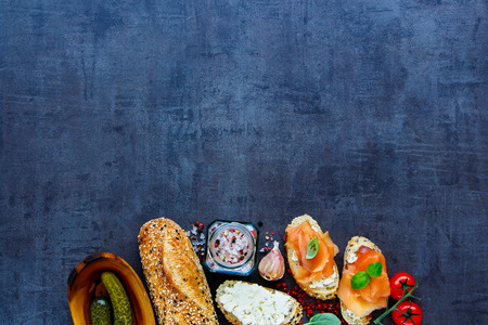Top view of sandwiches with smoked salmon, creamcheese, basil and fresh ingredients on vintage stone background. Flat lay style. Clean eating, weight loss food concept Stock Photo