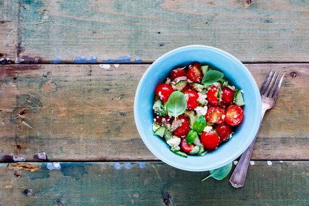 Healthy salad bowl with fresh summer vegetables and feta cheese on grunge wooden background. Weight loss clean eating, vegan, vegetarian, healthy, dieting food concept. Top view. With copy space.