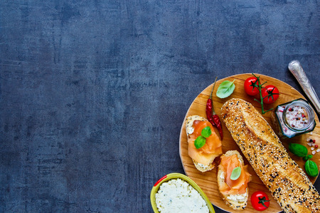 Sandwiches with smoked salmon, creamcheese, basil and fresh ingredients on round wooden board over vintage stone background. Top view. Clean eating, weight loss food concept Stock Photo