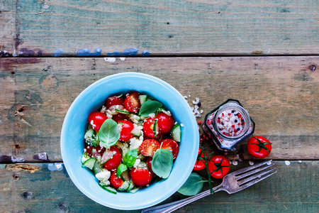 Top view of tasty summer vegetables and feta cheese salad in bowl on grunge wooden background. Weight loss clean eating, vegan, vegetarian, healthy, dieting food concept. Imagens