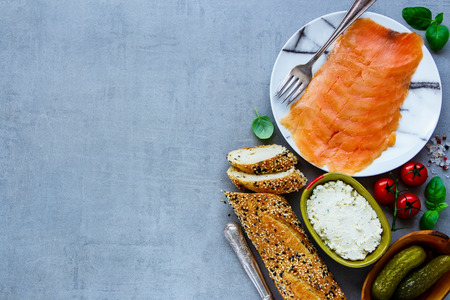 Fresh ingredients for making healthy sandwich. Baguette, smoked salmon, creamcheese, pickles and basil on grey concrete texture background. Top view. Clean eating, weight loss food concept
