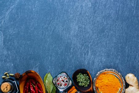 Dry herbs and spices selection for cooking on grey stone background, top view, copy space. Clean eating, vegan, detox, dieting, gardening or vegetarian food concept.