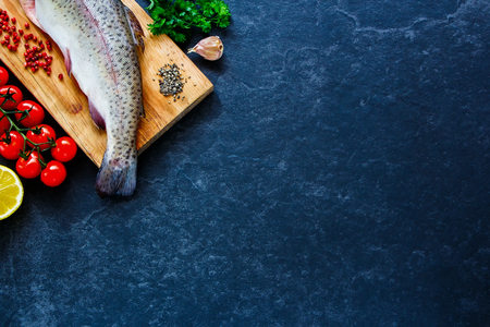 Delicious fresh seafood. Fish with ingredients - healthy food, diet or cooking concept. Whole raw fish on dark vintage texture. Food background, top view, flat lay style. Stock Photo
