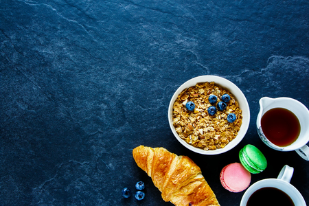 Breakfast concept on vintage table. Healthy breakfast of freshly baked croissant, homemade granola, coffee cup, berries, maple syrup and macaroons, top view, copy space Stok Fotoğraf