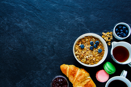 Delicious breakfast concept on vintage table. Healthy breakfast of freshly baked croissant, homemade granola, coffee cup, berries, strawberry jam and macaroons, top view, copy space Stok Fotoğraf