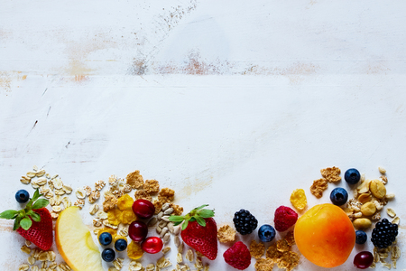おいしい朝食やスムージーの食材。さまざまな穀物、種子、新鮮な果実や白い素朴な背景に果物。健康的な朝食セットです。水平トップ ビュー