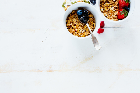 Breakfast table with white ceramic bowls of homemade granola, fresh berries and fruits on rustic background, copy space. Flat lay style. Healthy breakfast concept