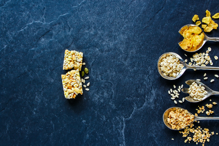 Healthy energy snack concept over slate texture. Granola bar and various cereals - corn flakes, oat flakes, granola and rice crisps in vintage spoons on dark backdrop, top view, copy space, horizontal