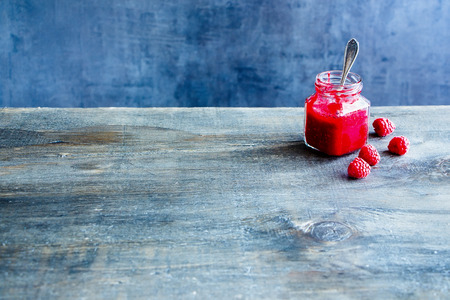 Homemade raspberry jam and fresh raspberries on vintage table, dark concrete wall background, copy space, selective focus Stock Photo