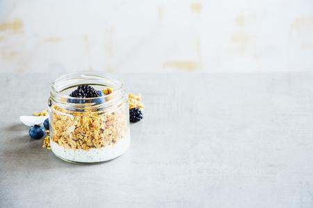 Summer breakfast in jar. Greek yogurt, granola, dark berry breakfast, white wooden wall background, copy space, selective focus. Clean eating, vegan, vegetarian, weight loss, healthy food concept