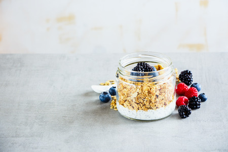 Tasty breakfast in jar. Greek yogurt, granola, fresh berry breakfast, white wooden wall background, copy space, selective focus. Clean eating, vegan, vegetarian, weight loss, healthy food concept Stock Photo