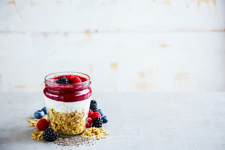Healthy detox breakfast. Greek yogurt, granola, fresh berry breakfast in jar, white wooden wall background, copy space, selective focus. Clean eating, vegan, vegetarian, weight loss, healthy food concept