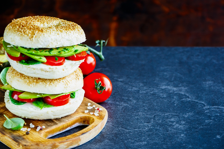 Healthy food. Heap of bagels with avocado, cream-cheese, tomatoes and basil, rustic wooden wall background, selective focus. Clean eating, vegan, vegetarian, weight loss, healthy food concept