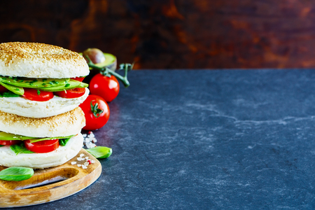 Food. Heap of healthy bagels with avocado, cream-cheese, tomatoes and basil, rustic wooden wall background, selective focus. Clean eating, vegan, vegetarian, weight loss, healthy food concept